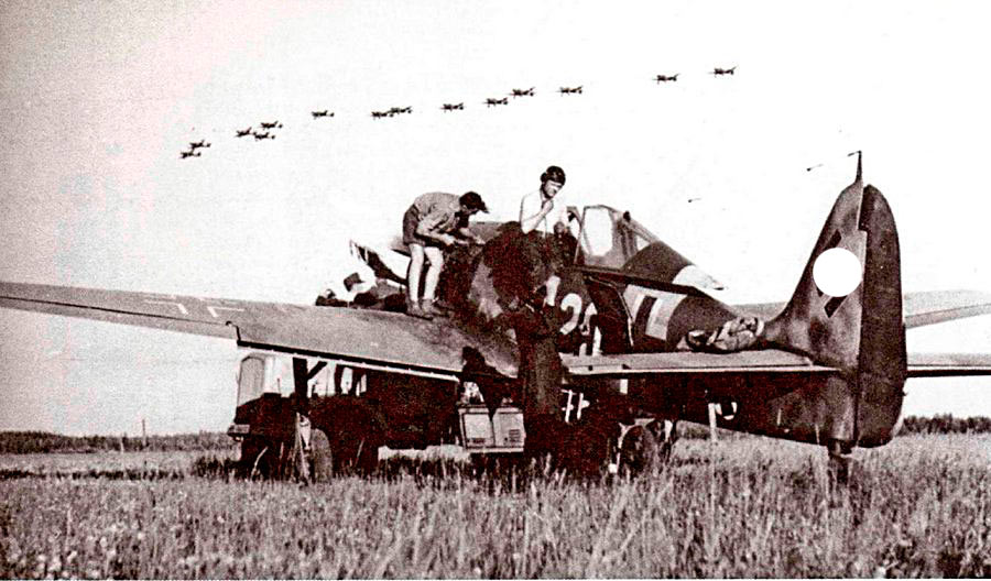 Группа пикирующих бомбардировщиков Ju-87 в воздухе ждет когда взлетят их истребители сопровождения.