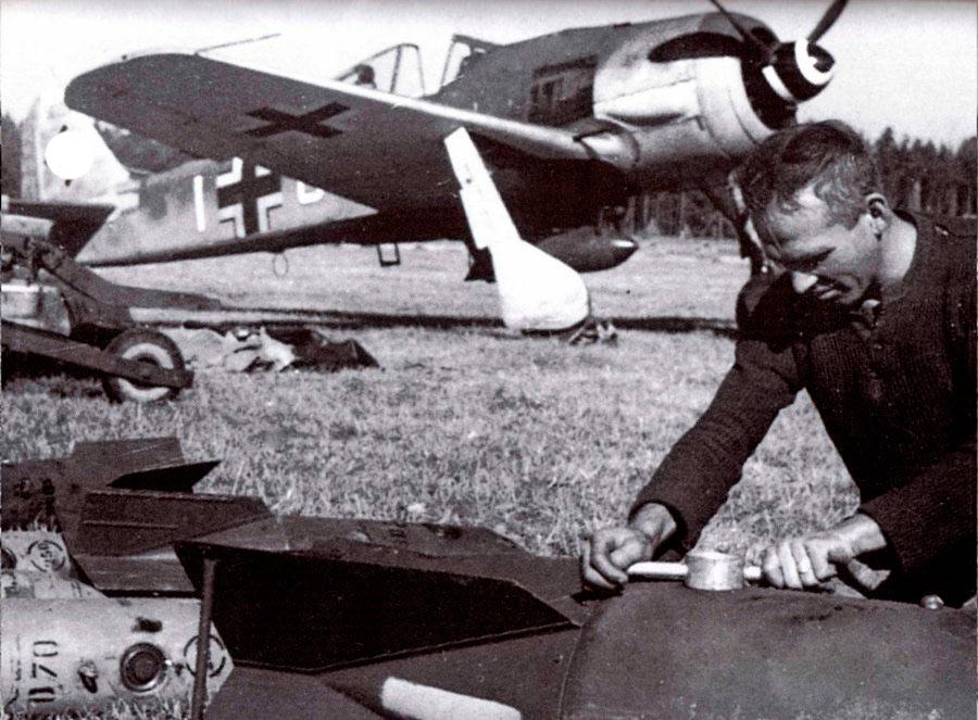 Техник по вооружению закручивает взрыватель на бомбе SC250, а на заднем плане истребитель-бомбардировщик FW-190F-9. Эта модель не имеет крыльевых пушек, зато таскает под брюхом бомбы и имеет измеритель давления на правом крыле.