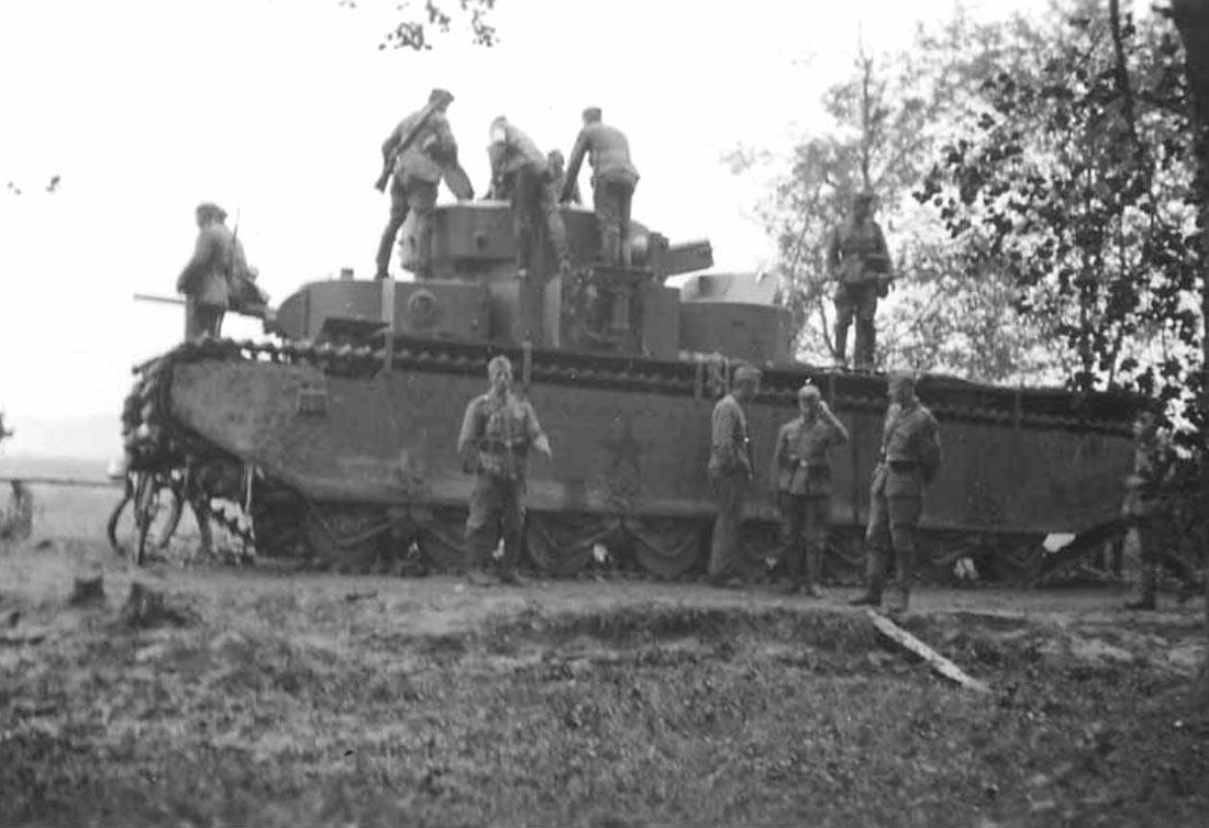 Немецкие солдаты осматривают советский танк Т-35 брошенный на трассе в 5 км. от г.Сасов