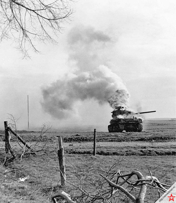 Горящий американский танк «Шерман» 3-й танковой дивизии США, подбитый немецкой артиллерией в Бергерхаузене, Керпен, Германия. Модификация танка M4A1(76)W, в отличие от «Шерманов» передававшихся СССР по ленд-лизу M4A2, имевшая не дизель, а бензиновый двигатель. Англичане даже обзывали танки этого типа «Ронсон», по названию популярной бензиновой зажигалки.