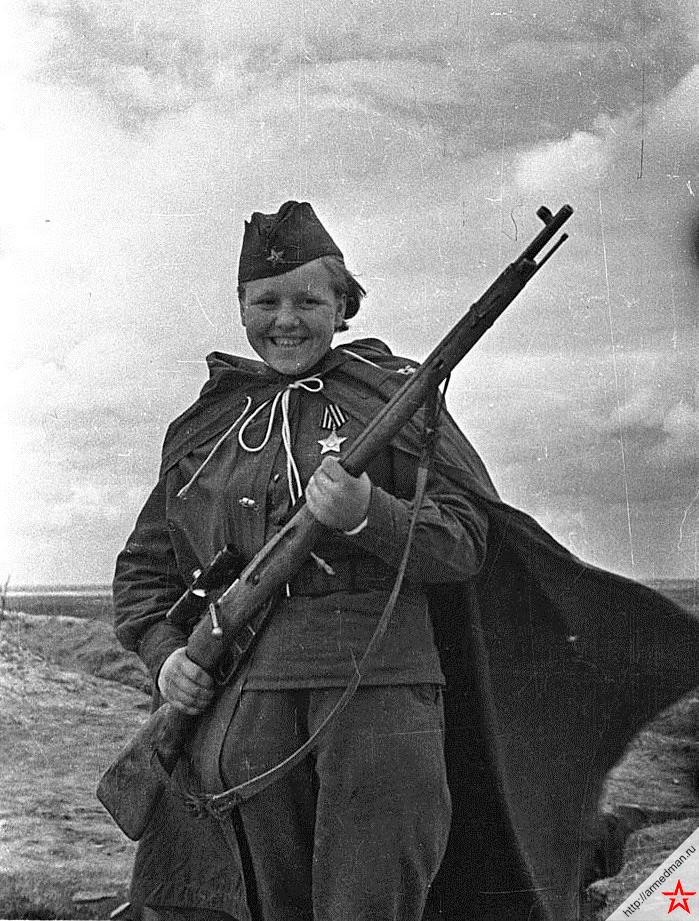 Кавалер ордена «Славы» 3 степени, снайпер Мария Кувшинова, уничтожившая 23 немецких солдата и офицера. На момент прибытия на фронт её было 16 лет (приписала 3 года).  Мария Григорьевна прошла через освобождение Орши, Минска, взятие Кенигсберга и прорыв обороны противника в районе Мазурских озер, после войны работала в Нижнем Тагиле на металлургическом комбинате и воспитывала двоих сыновей. Снимок сделан в мае 1944 года Михаилом Савиным.
