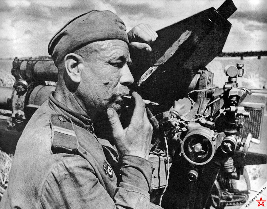 Советский артиллерист-гвардеец отдыхает у своей 122-мм гаубицы М-30 после боя с немецкими танками под Каунасом. 3-й Белорусский фронт. Осень 1944 года